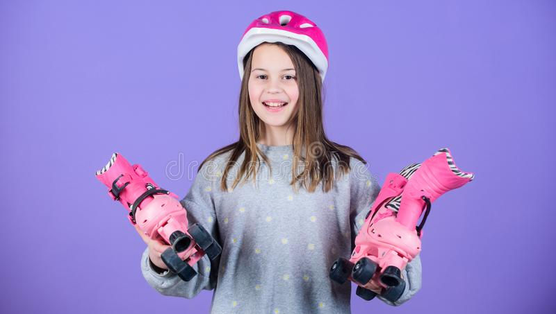 Ready to roller skating. Girl cute teen wear helmet and roller skates on violet background. Active leisure and lifestyle. Roller skating teen hobby. Joyful stock photo