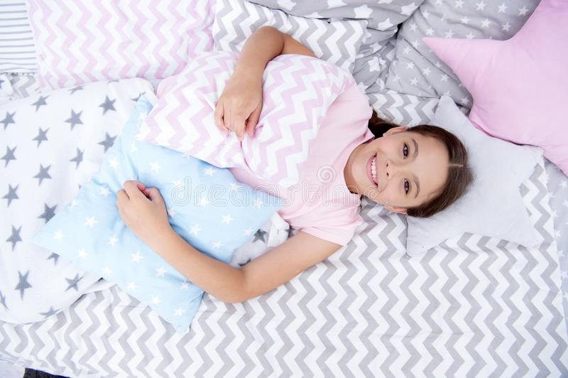 Ready to sleep. Girl smiling happy child lay on bed with star shaped pillows and cute plaid in her bedroom. Bedclothes royalty free stock photography
