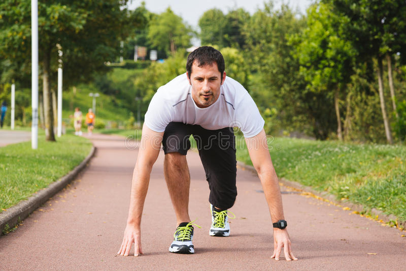 Ready to sprint. Attractive sportsman ready to sprint in a sports area outdoors stock photography