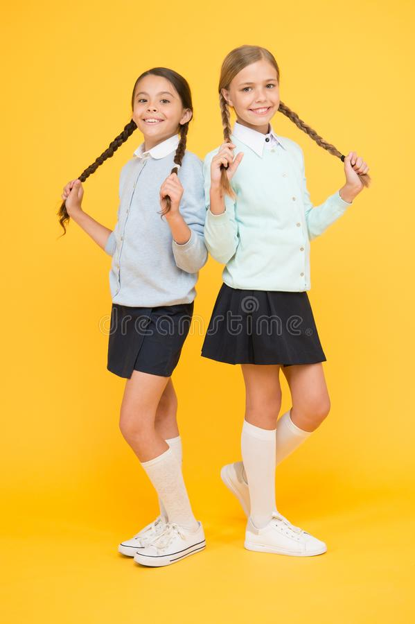 Ready to study. education concept. back to school. smart little girls on yellow background. happy girls in school stock photography