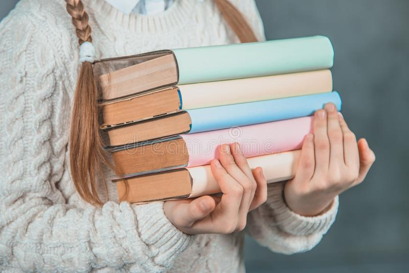Ready to study hard Strong smart girl is holding books and is isolated on grey background. Ready to study hard Strong smart girl with fashionable and royalty free stock image