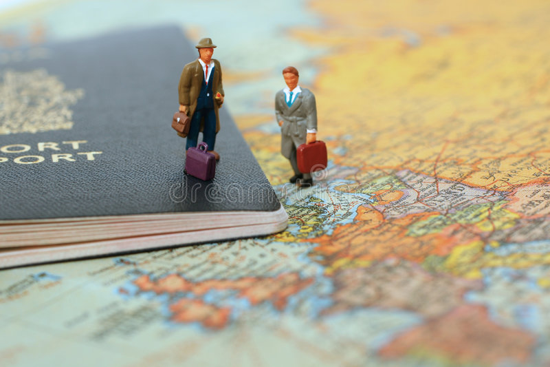 Ready to travel. Mini people standing on canadian passport and world map ready to travel