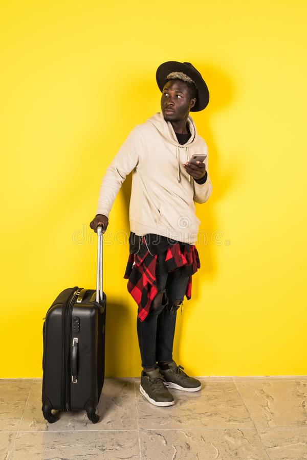 Ready to travel. Cheerful happy african man holding his luggage while being ready to travel stock images