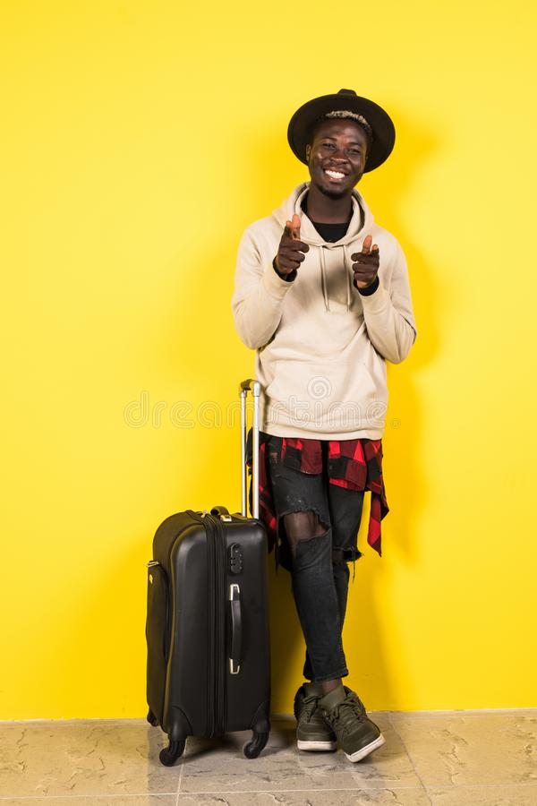 Ready to travel. Cheerful happy african man holding his luggage while being ready to travel stock photo