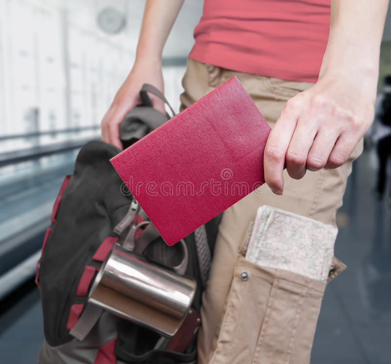 Ready to travel!. Unrecognizable woman is standing with a passport and a backpack at the airport stock photos