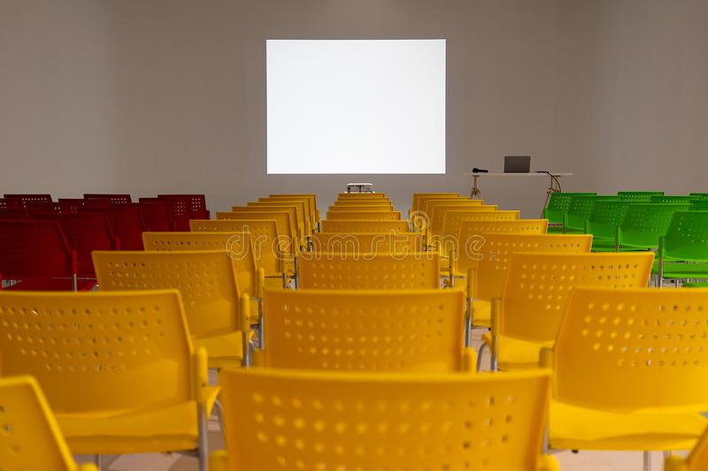 Ready to use rows of colorful chairs in conference room with blank white space on wall as projector screen. Ready to use rows of colorful chairs in conference stock photo
