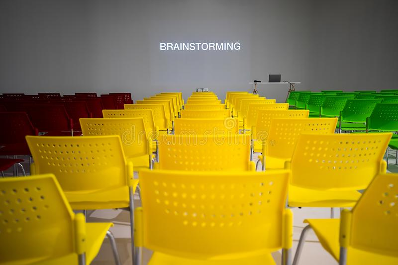 Ready to use rows of colorful chairs in conference room with words brainstorming on wall as projector screen. And laptop on table royalty free stock photos