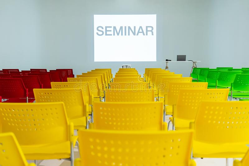 Ready to use rows of colorful chairs in conference room with words seminar on wall as projector screen. And laptop on table royalty free stock photo