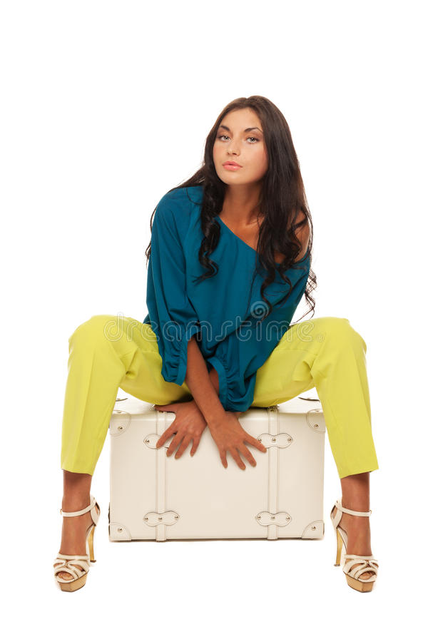 Ready for vacations. Girl sitting on case on isolated white stock image
