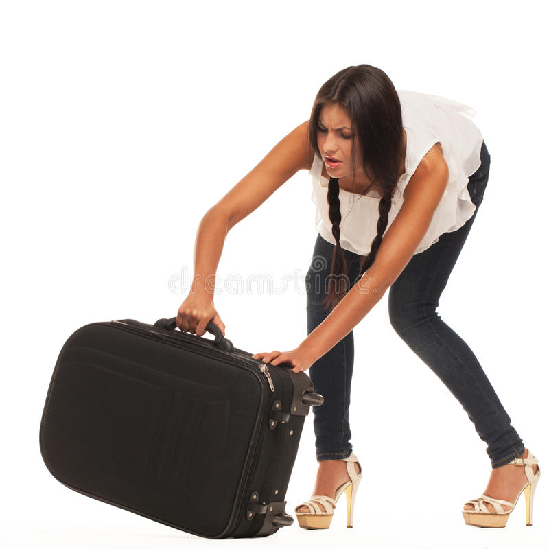Ready for vacations. Girl is trying to lift her luggage up (isolated, standing on white surface royalty free stock image