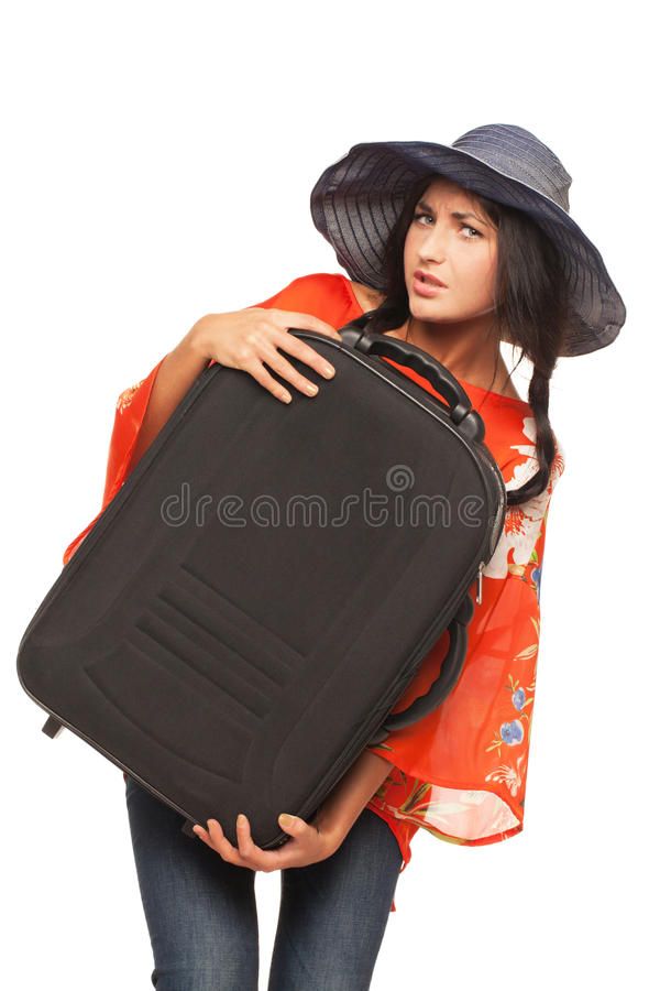Ready for vacations. Girl is trying to lift her luggage up stock photography