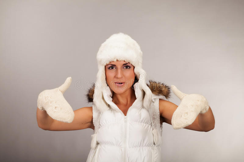 Ready for the winter. Girl with mittens and fur hat looking straight in camera royalty free stock image