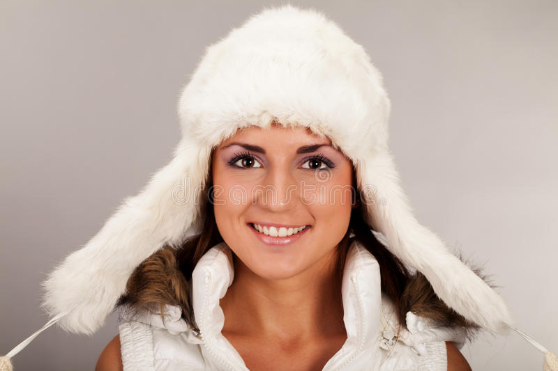 Ready for the winter. Girl with mittens and fur hat looking straight in camera stock image