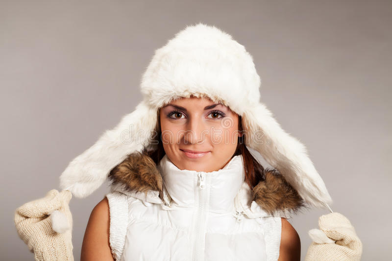 Ready for the winter. Girl with mittens and fur hat looking straight in camera royalty free stock images