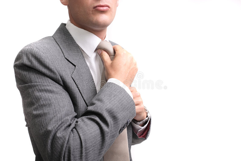 Ready for work. Young businessman fastening tie, isolated over white background royalty free stock photos