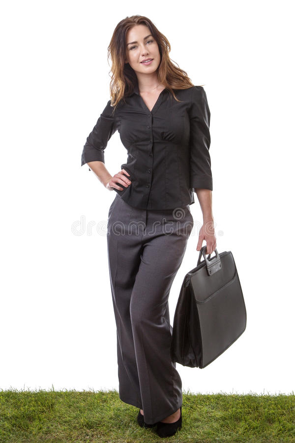 Ready for work. Business model holding a briefcase in one hand, standing on grass stock photos