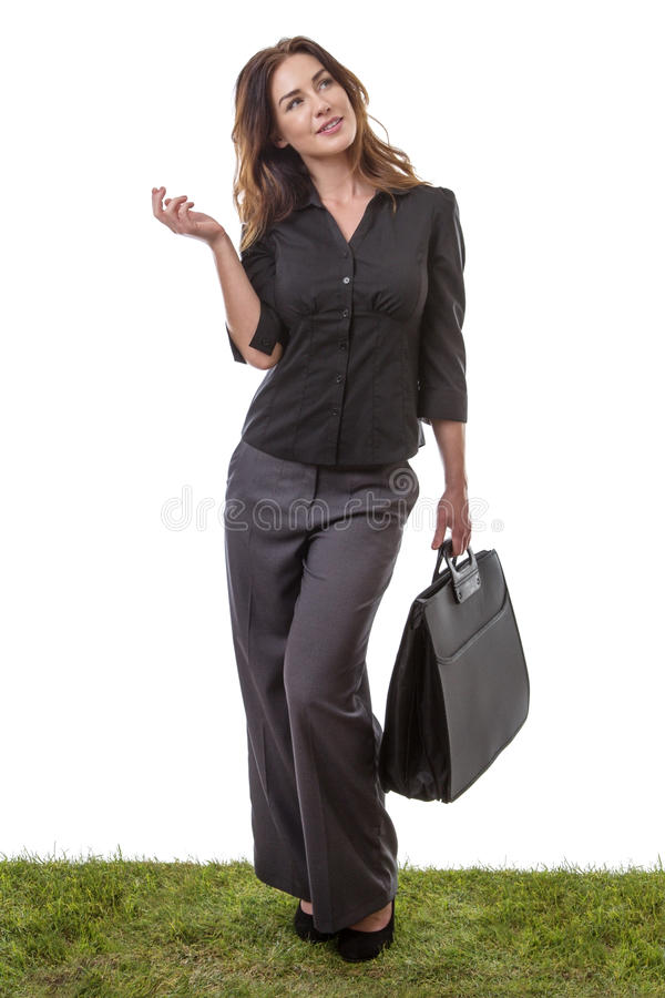 Ready for work. Business model holding a briefcase in one hand, standing on grass stock images