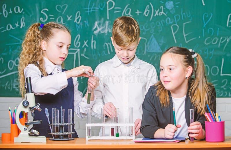 Reagenzgl?ser mit Substanzen Schulbildung M?dchen und Jungenstudentenf?hrungsschulexperiment mit Fl?ssigkeiten schule stockfotos