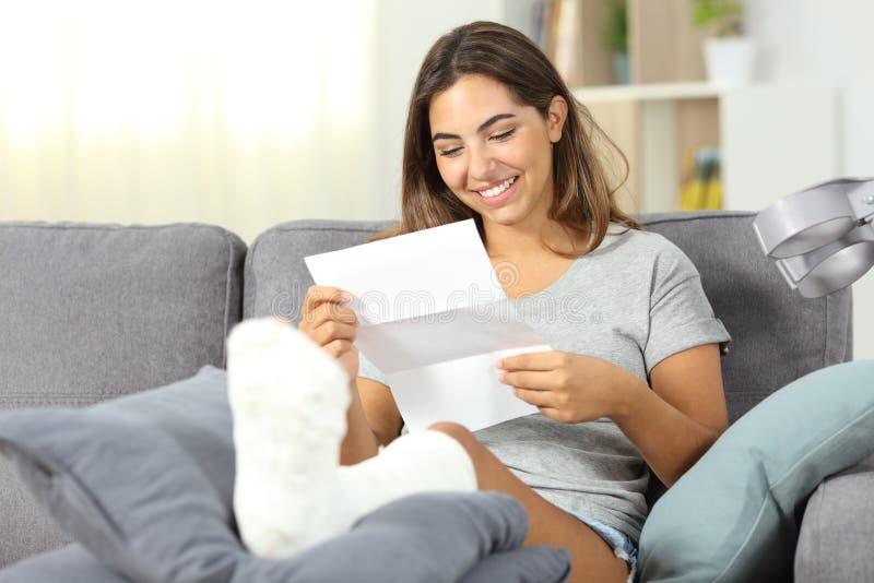 Reaidng heureux de femme handicapée une lettre images stock