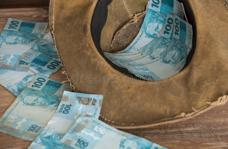 Reais brasileiros do dinheiro, com chapéu Conceito da fraude financeira imagens de stock royalty free