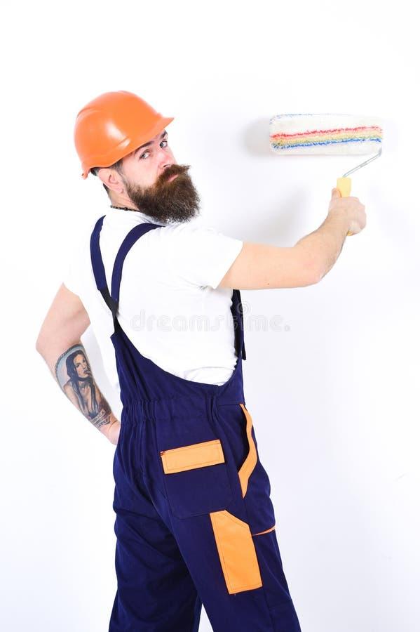 Reajuste y reparación del apartamento Devuelva el contratista en el casco anaranjado que se coloca con el rodillo de pintura en s imagen de archivo libre de regalías