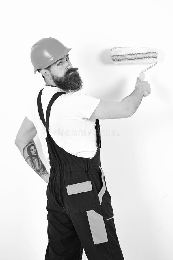 Reajuste y reparación del apartamento Devuelva el contratista en el casco anaranjado que se coloca con el rodillo de pintura en s foto de archivo