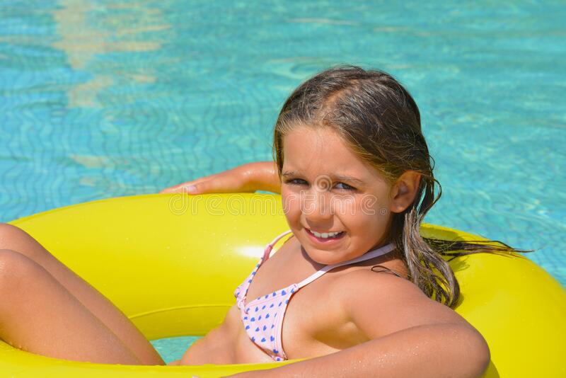 Real adorable girl relaxing in swimming pool royalty free stock photography