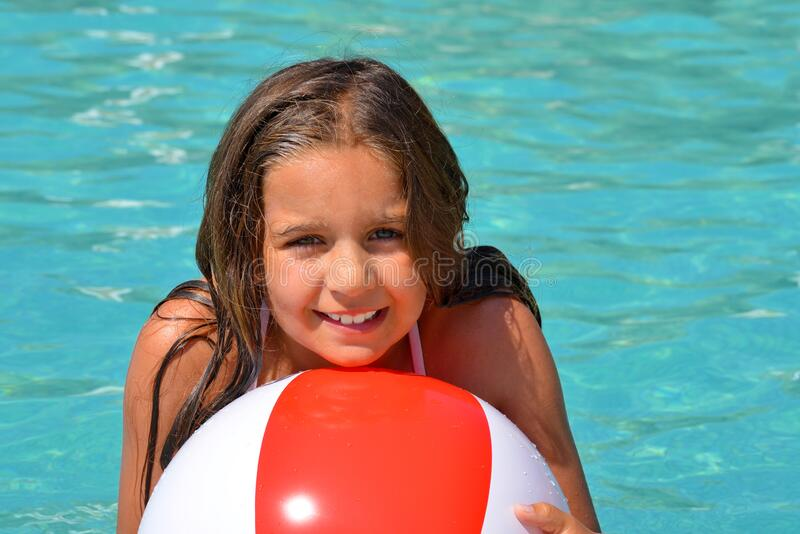 Real adorable girl relaxing in swimming pool royalty free stock photo
