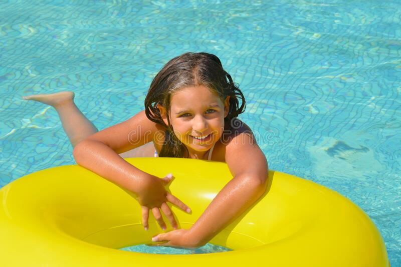 Real adorable girl relaxing in swimming pool stock photography