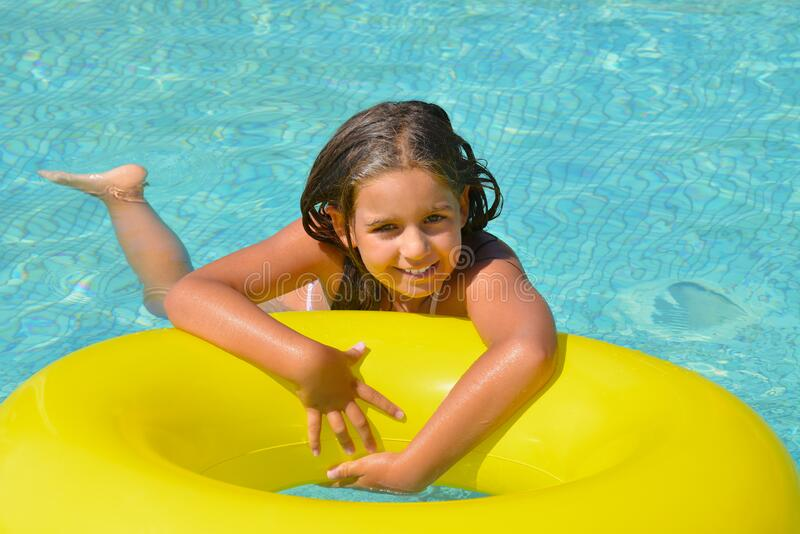 Real adorable girl relaxing in swimming pool stock image