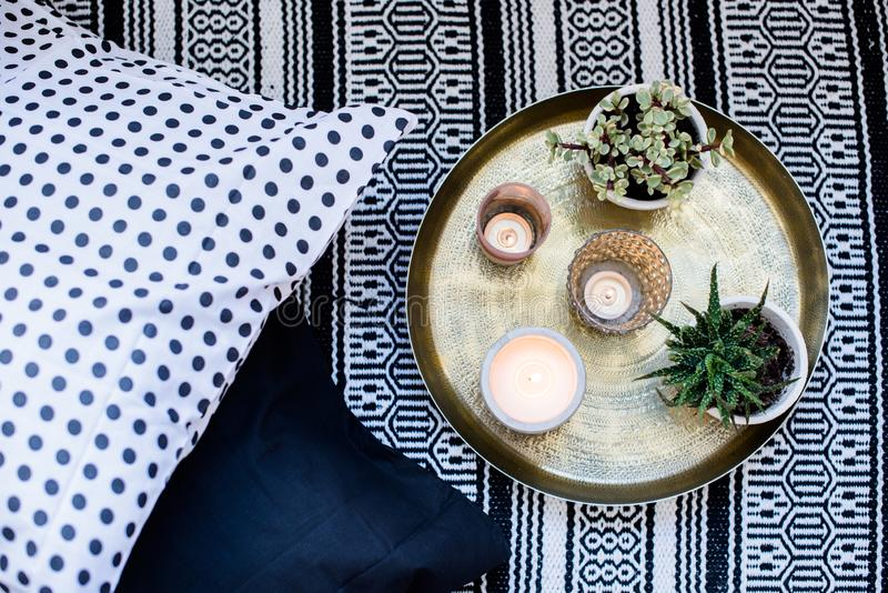 Real apartment interior decor, aromatic candles and plants on vintage tray with pillows and carpet on the floor stock photography