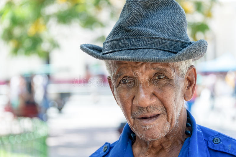 Real Cuban people in the street: Afro Caribbean man-Santa Clara. Cuban real people faces. Man in outdoor urban area in daytime. Portrait of an old man wearing stock image