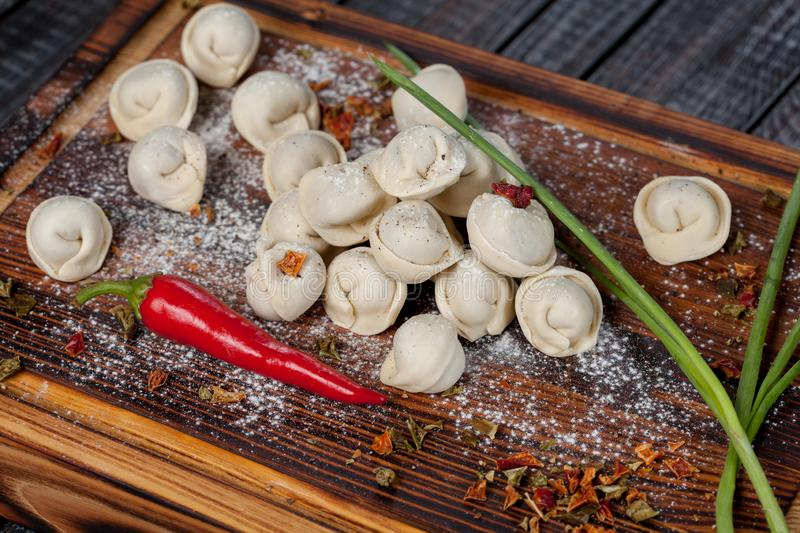 Real, delicious, Russian dumplings on the table, with fresh herbs and spices royalty free stock image