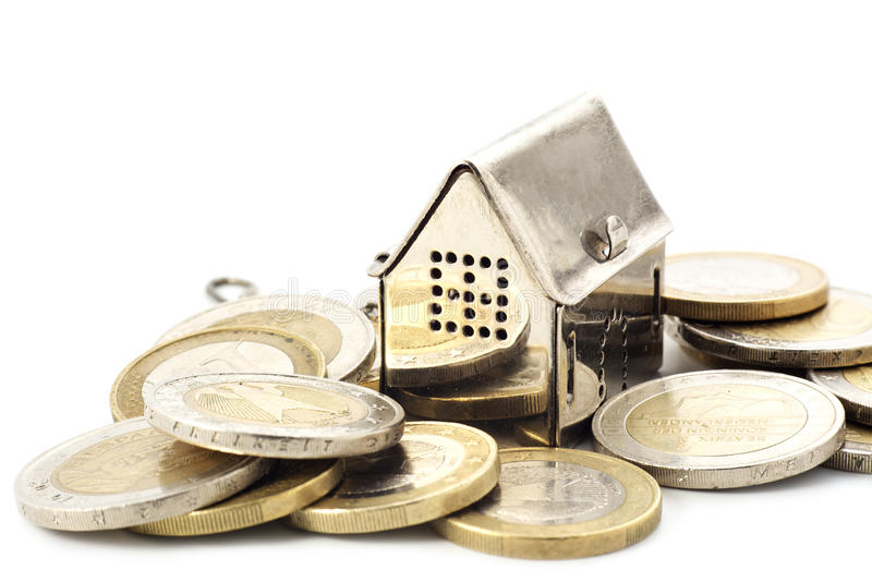 Real estade background, little house in a heap of coins isolated. Concept background for real estate, little slilver golden house in a heap of coins against stock image