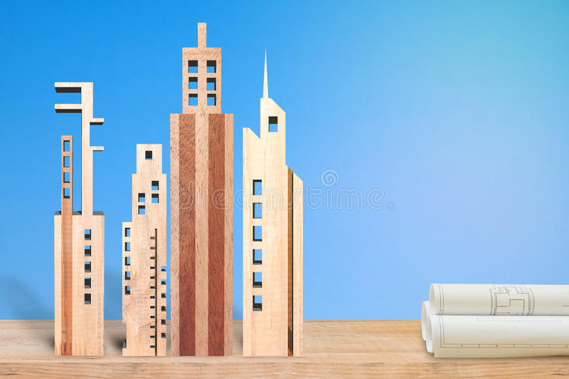 Real estage concept. Miniature building made from wood on blue background. Real estate concept stock photography