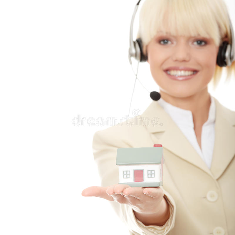Real estate. Young businesswoman in headset holding two hose models royalty free stock photos