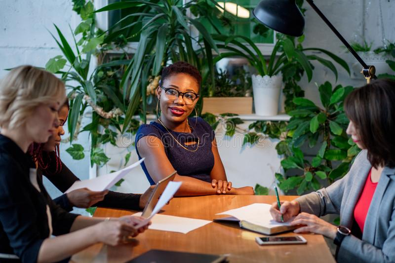 African female manager consulting women at her office promising benefits stock photography