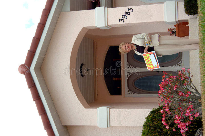 Real estate agent. A real estate agent with for sale sign in front of home royalty free stock photography