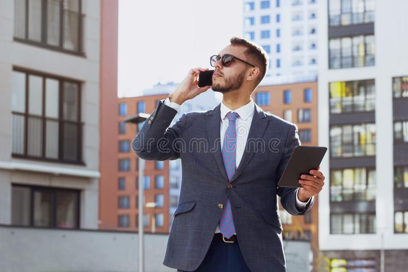 Real estate agent businessman city phone calling. Real estate agent on background of modern city. Businessman is talking by mobile phone royalty free stock photography