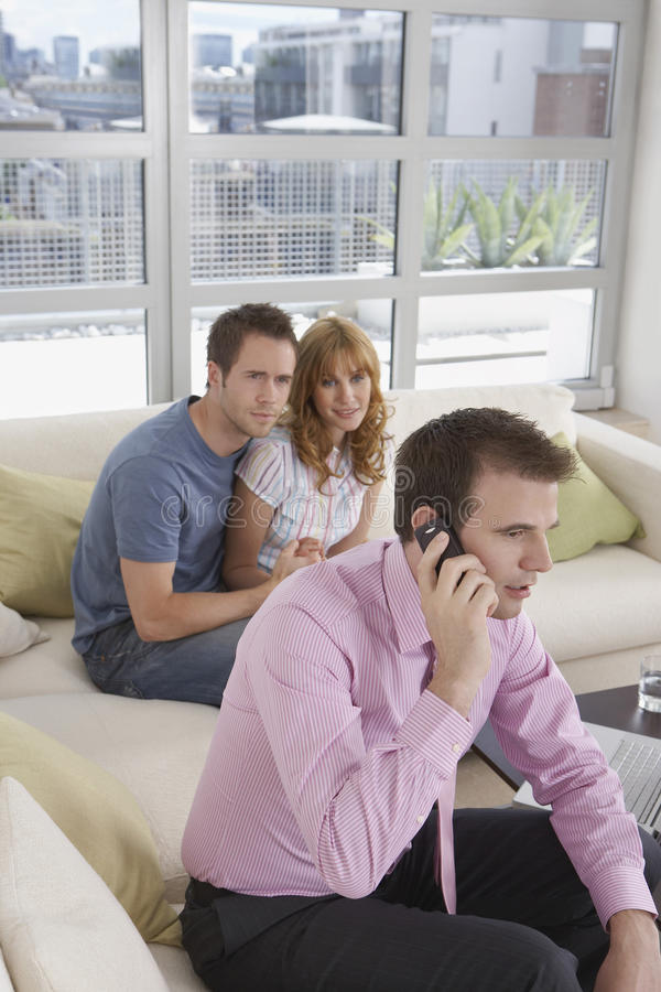 Real Estate Agent On Call By Couple In New Home. Male real estate agent using mobile phone by couple in new home stock photo
