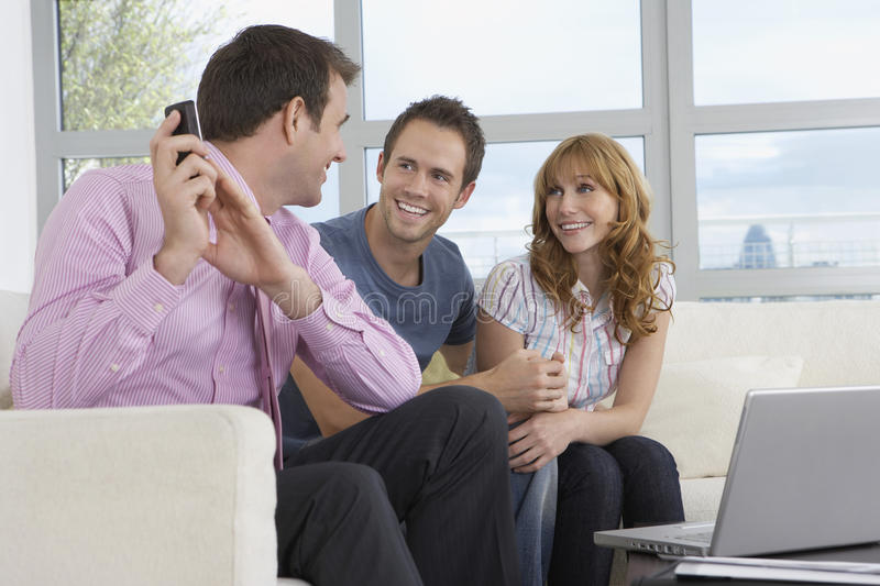 Real Estate Agent On Call By Couple In New Home. Smiling male real estate agent using mobile phone by couple in new home royalty free stock photo