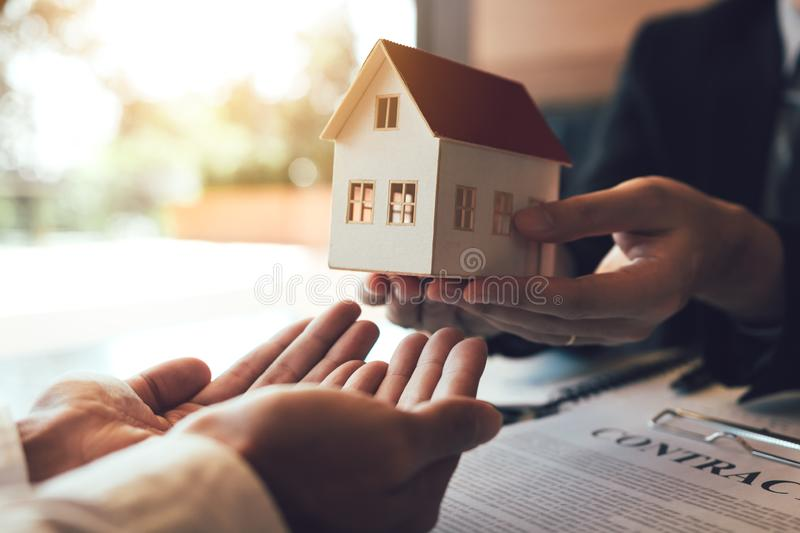 Real estate agent congratulations to new buyer by giving house model to client in the agency office stock image