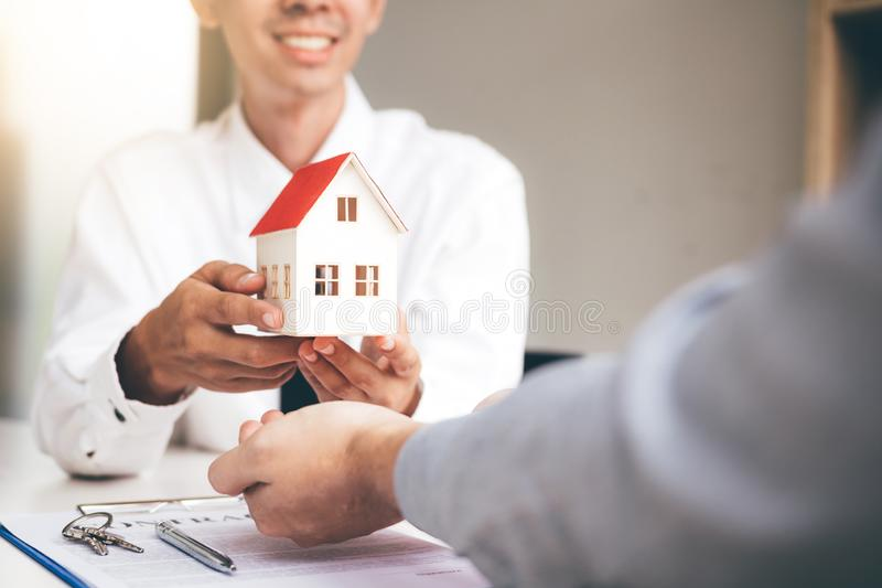 Real estate agent congratulations to new buyer by giving house model to client in the agency office.  royalty free stock images