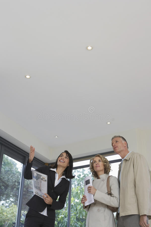 Real Estate Agent And Couple Observing New Property. Female real estate agent and couple observing new property stock photos