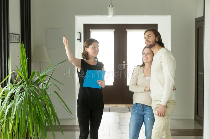 Real estate agent or designer showing house to young couple. Real estate agent showing house to couple, realtor telling clients about home advantages, interior royalty free stock photography