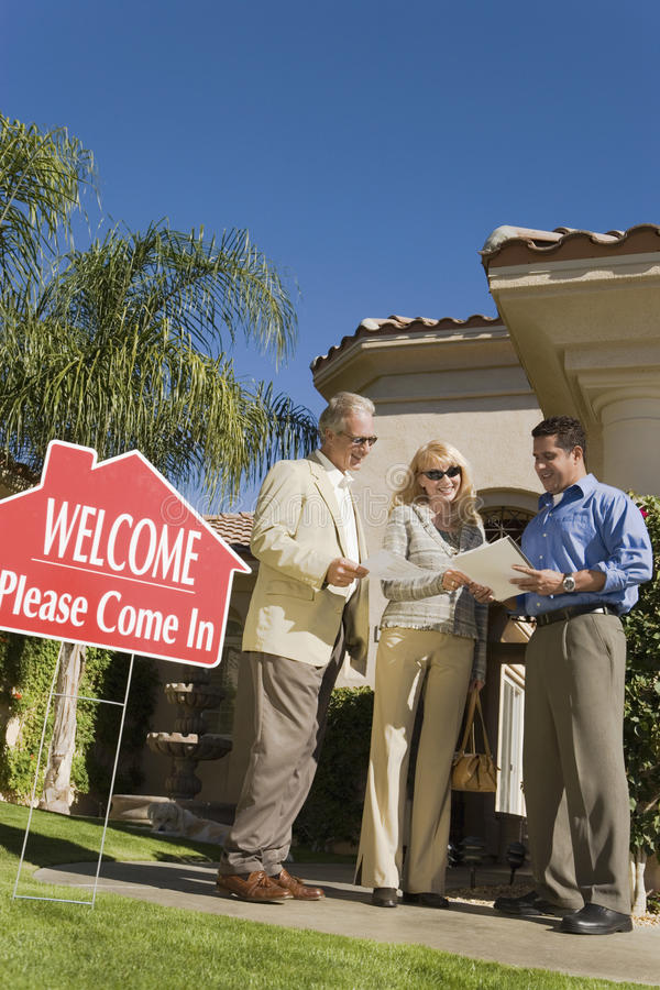 Real Estate Agent Discussing Contract With Couple stock photo