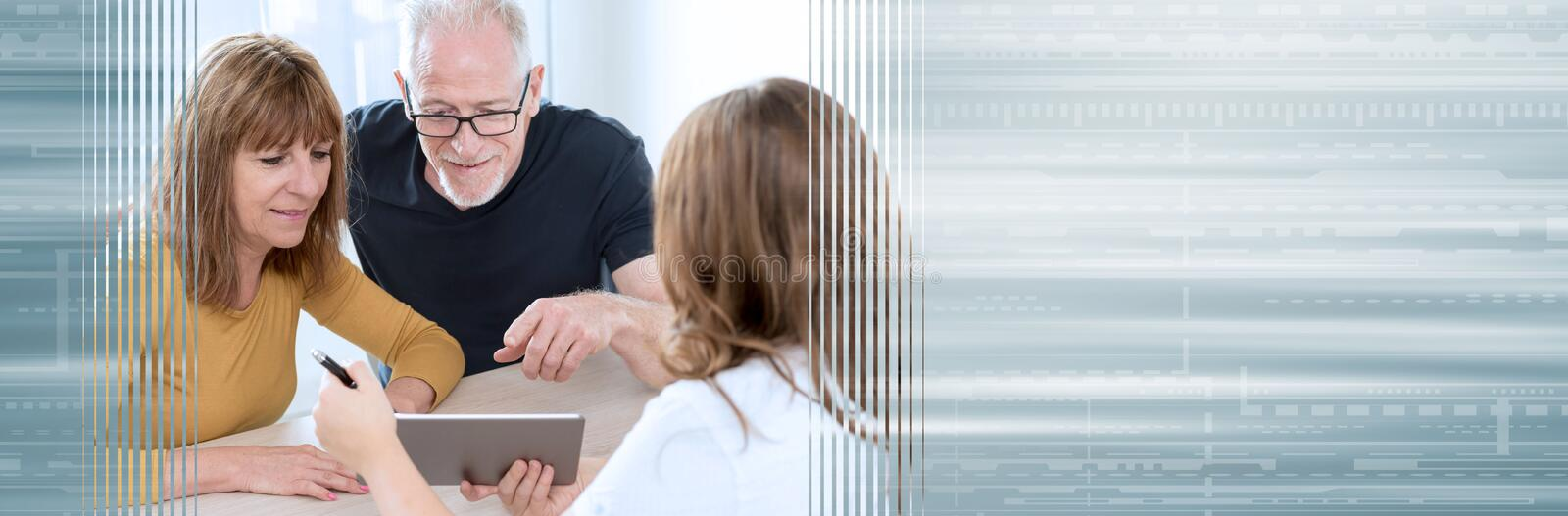 Senior couple meeting real estate agent. panoramic banner. Real estate agent giving explanations on tablet to senior couple. panoramic banner royalty free stock images
