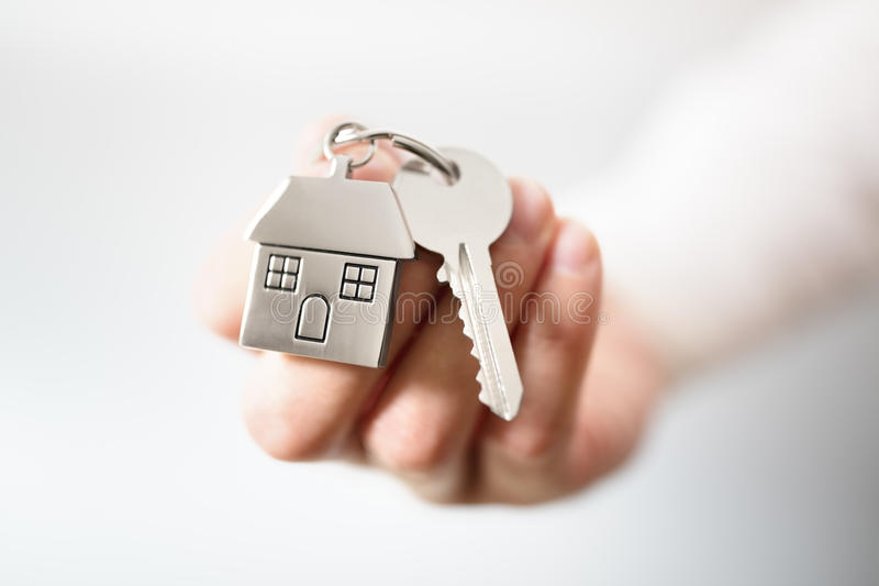 Real estate agent giving house keys. Holding house keys on house shaped keychain concept for buying a new home royalty free stock photo