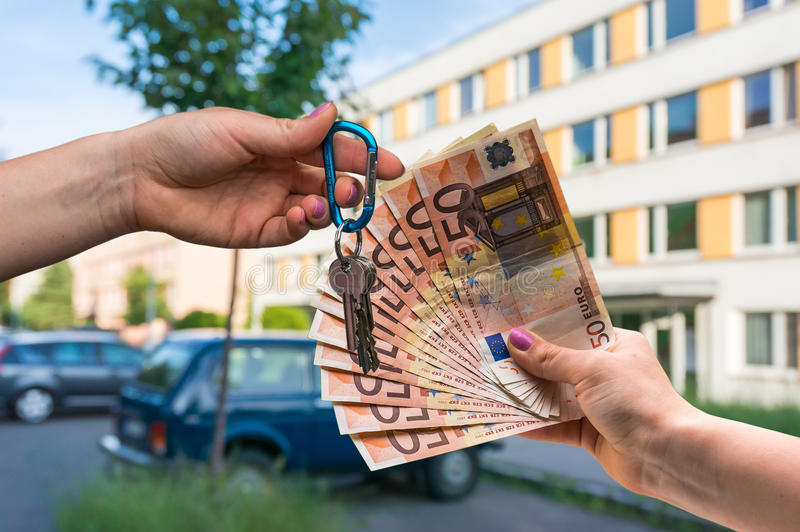 Real estate agent giving house keys to a new property owner, who. Is paying by euro money on blurred background stock images