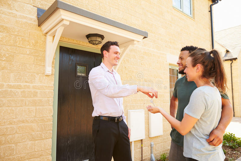 Real estate agent giving house keys to new property owners royalty free stock images